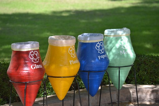 Four brightly coloured recycling barrels outside the workplace